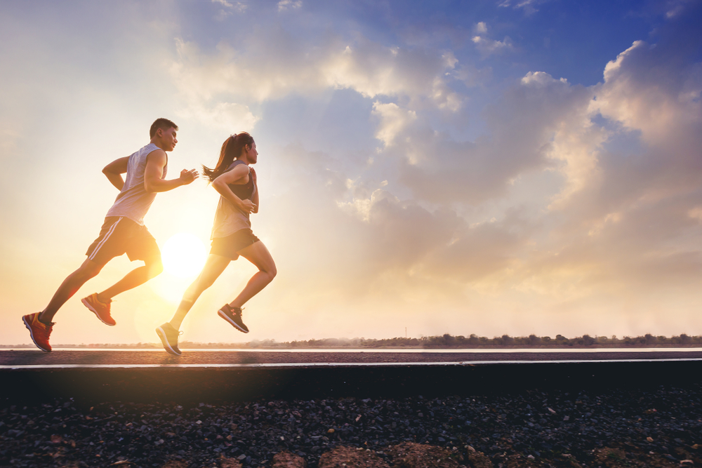 Male and female runners with a sunset behind them.